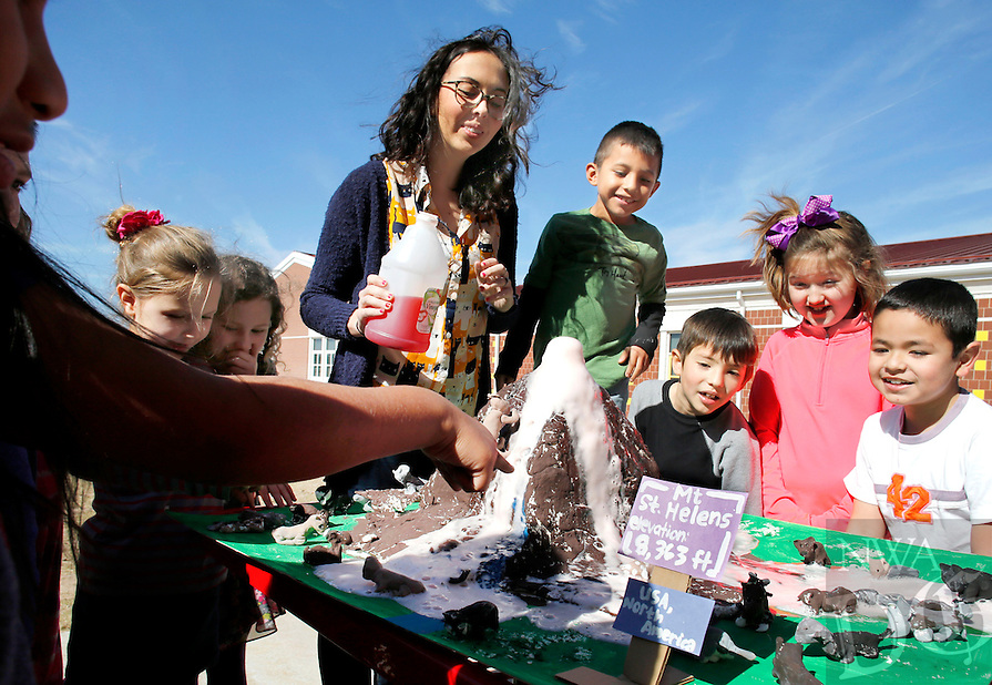 NWA Democrat-Gazette/DAVID GOTTSCHALK  Art teacher Carly Cartmill (center) watches pink lava Thursday, February 18, 2016, flow from a volcano with her second grade students at Sonora Elementary School. The students created a replica of Mount St. Helens in their art class as part of a study on the forces of nature.