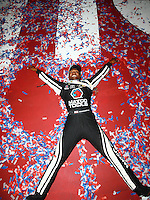 Nov 13, 2016; Pomona, CA, USA; NHRA top fuel driver Antron Brown celebrates doing snow angels in the confetti following the Auto Club Finals at Auto Club Raceway at Pomona. Mandatory Credit: Mark J. Rebilas-USA TODAY Sports