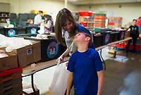 NWA Democrat-Gazette/CHARLIE KAIJO Hannah Dunlap of Lowell (from center left) and Mason Dunlap, 7, help prepare snack packs, Thursday, March 22, 2018 at the Samaritan Community Center in Rogers. <br />