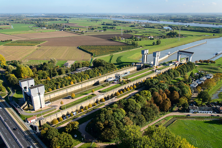 Nederland, Gelderland, Tiel, 24-10-2013; Betuweroute en autosnelweg A15 kruisen het Amsterdam-Rijnkanaal ter hoogte van de Prins Bernhardsluis,rivier de Waal in de achtergrond. Goederentrein nadert de brug over het kanaal. Binnenvaartschepen in de sluiskolk.<br /> Betuweroute, railway from Rotterdam to Germany,  and A15 motorway cross the Amsterdam-Rhine Canal at the Prince Bernhard lock, the Waal river in the background. Freight train on its way to the bridge over the canal. Barges in the lock chamber.<br /> luchtfoto (toeslag op standaard tarieven);<br /> aerial photo (additional fee required);<br /> copyright foto/photo Siebe Swart.