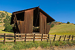 Wooden, weathering red trapezoidal feeding barn along Dry Creek, Sierra Nevada Foothills, Tulare Co., Calif.
