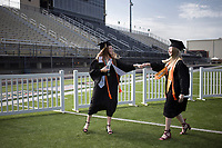 Graduates Shae Spear (from left) and Jaide Yoes fist bump, Friday, July 17, 2020 during a graduation ceremony at Bentonville High School in Bentonville. Check out nwaonline.com/200718Daily/ for today's photo gallery. <br /> (NWA Democrat-Gazette/Charlie Kaijo)