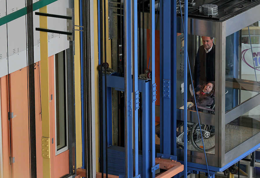 William Massart, right, and his daughter Sandra Massart, 10, ride the elevator at Duke University Hospital in Durham, NC, USA, on Tuesday, Feb. 14, 2012.  Sandra Massart is being treated for MLD, a degenerative condition.  Photo by Ted Richardson