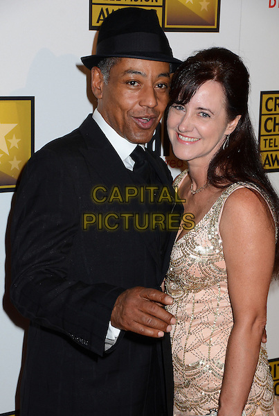 Giancarlo Esposito & guest.2nd Annual Critic's Choice Television Awards Presented by the Broadcast Television Journalists Association held at the Beverly Hilton, Beverly HIlls, California, USA..June 18th, 2012.half length black suit hat pink silver dress.CAP/ADM/BT.©Birdie Thompson/AdMedia/Capital Pictures.