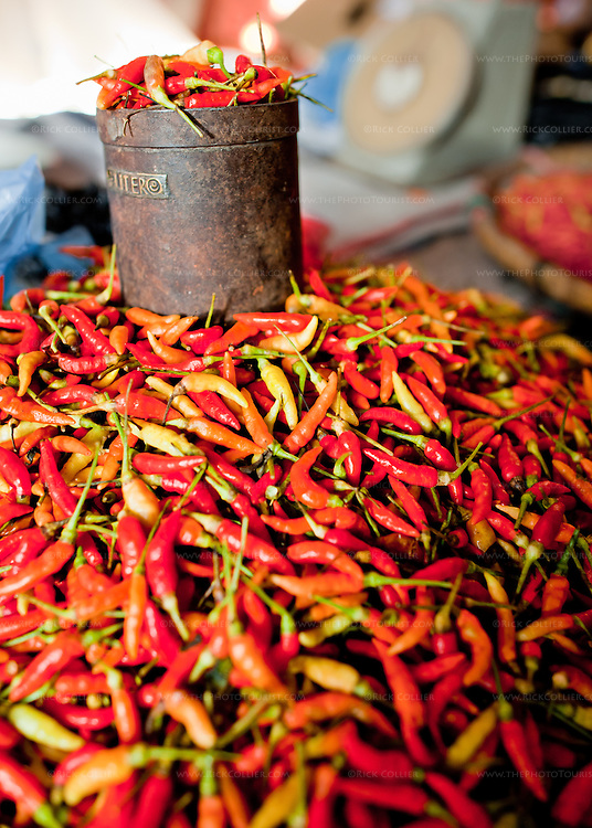Hot peppers are a staple in Indonesian cooking.  Peppers for sale in the market are usually displayed in a pile.  Of course, there is also always a container for measuring the goods into a bag when a sale is negotiated.  (Photo from the market in Bitung, North Sulawesi, Indonesia.)