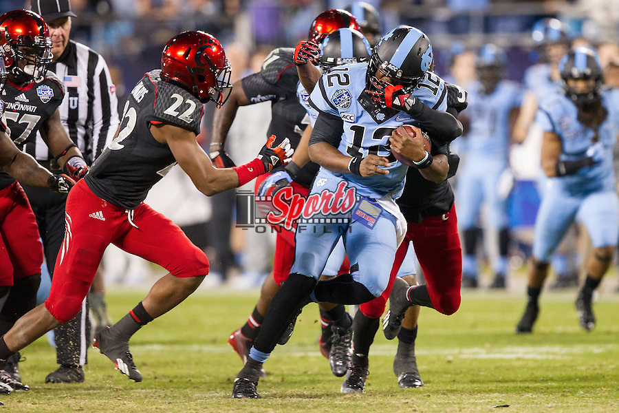 Marquise Williams (12) of the North Carolina Tar Heels has his facemask grabbed by Aaron Brown (5) of the Cincinnati Bearcats in the Belk Bowl at Bank of America Stadium on December 28, 2013 in Charlotte, North Carolina.  The Tar Heels defeated the Bearcats 39-17.   (Brian Westerholt/Sports On Film)