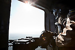 11/12/2014. Fishkhabour, Iraq. The door gunner of an Iraqi Air Force Mi-171E Hip helicopter keeps watch during a mission to resupply peshmerga, PKK and Yazidi refugees trapped on Mount Sinjar.<br /> <br /> Although a well publicised exodus of Yazidi refugees took place from Mount Sinjar in August 2014 many still remain on top of the 75 km long ridge-line, with estimates varying from 2000-8000 people, after a corridor kept open by Syrian-Kurdish YPG fighters collapsed during an Islamic State offensive. The mountain is now surrounded on all sides with winter closing in, the only chance of escape or supply being by Iraqi Air Force helicopters.