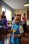 Matthew is fascinated by the clowns and their magic tricks. Oncology ward at the Royal Manchester Children hospital.