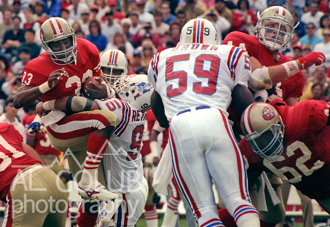 San Francisco 49ers vs New England Patriots at Stanford Stadium Sunday, October 22, 1989..49ers Beat Patriots 37-20.49er running back Roger Craig (33)  attempts to break away from Patriots linebacker Ed Reynolds (95) ..
