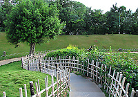 Stock photo of spiral wooden railing and steps leading downwards in garden.