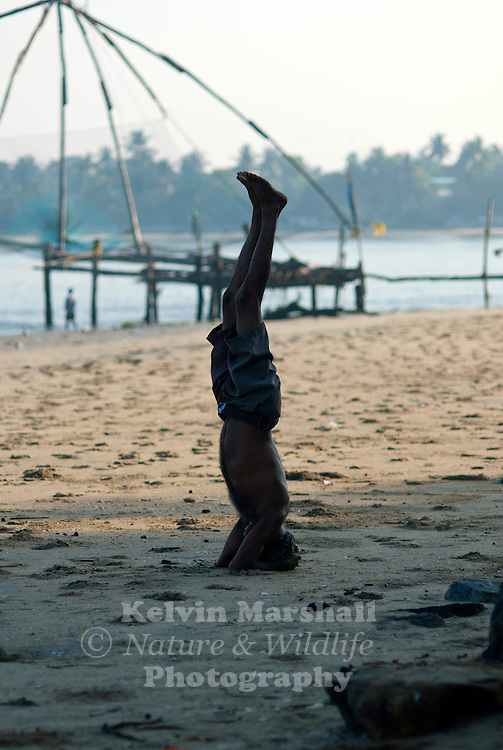 A local fisherman exercises on the beach. Cochin fishing village, - Kerala, Southern India.