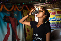 A teenage girl drinks water in Ambedkar Nagar in Medak, Telangana, India.
