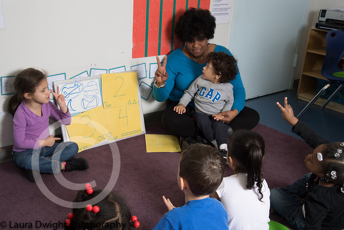 Education Preschool Childcare 2-3 year olds circle time group with female teacher, children holding up fingers for number 2