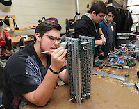 STAFF PHOTO ANDY SHUPE - Brayden Rose, 16, left, replaces parts on a robot component as Noah Wehn, 16, center, and Juan Zuniga speak while working on the team's robot Thursday, Dec. 18, 2014, at Southwest Junior High School in Springdale. The students are sophomores at Har-Ber High School, but drive to Southwest Junior High School to use the school's workroom since Har-Ber lacks a similar facility.