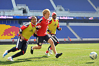 Tyler Lassiter (12) (C)  of the New York Red Bulls races to a ball under pressure from Juan Agudelo (17) (L) and Tony Tchani (23) (R) during practice on Media Day at Red Bull Arena in Harrison, NJ, on March 15, 2011.