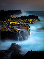 At sunset, water spills off of the rocks of Keahole Point, Big Island.