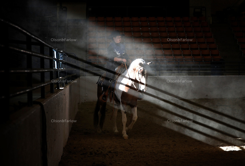 Morning sun casts dramatic light on a rider in the Western States Wild Horse and Burro Expo that attracts mustang lovers from Nevada and California to compete with their adopted horses.    Eighty six participants entered Western pleasure, showmanship, barrel racing as well as costume and the champagne race (to not spill a cup of water while riding).