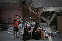 "In this Saturday, Aug. 16, 2014 photo, a Palestinian family sit at the entrance of their house after it was partially distroyed by artillery shelling during the ""Protective Edge"" Israeli military operation in Beit Hoanoun neighborhood in Gaza City. After a five days truce was declared on 13th August between Hamas and Israel, civilian population went back to what remains from their houses and goods in Gaza Strip. (Photo/Narciso Contreras)"