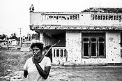 54 year old Kanagisweri stands outside her house destroyed during the last battle between the LTTE and the Sri Lankan army along the highway in Kilinochchi, in northern Sri Lanka. Photo: Sanjit Das/Panos