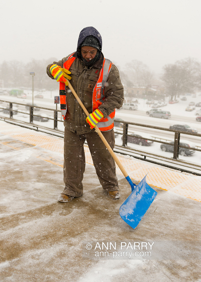 Merrick, New York, U.S. January 21, 2014. Maintenance of Way (MOW) workers for the Metropolitan Transit Authority (MTA) shovel snow as it falls heavily on the windy elevated platform of the Merrick Train Station. The Metropolitan Transit Authority added extra afternoon trains to Long Island Rail Road. Long Island towns declared a snow emergency, with up to 10 inches of snow expected.