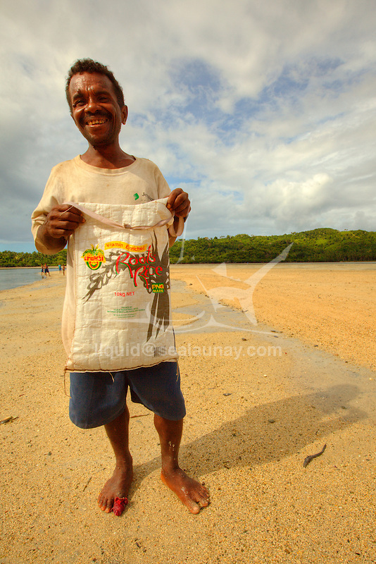 """A man going to harvest sea cucumbers in the village of Hessessai Bay at PanaTinai (Panatinane)island in the Louisiade Archipelago in Milne Bay Province, Papua New Guinea.  The island has an area of 78 km2..Sea cucumbers are marine animals of the class Holothuroidea that are used in fresh or dried form in various cuisines. The creature and the food product is commonly known as bêche-de-mer (lit. """"sea-spade"""") in the French language, trepang (Malay tr?pang) in Malaysian, namako in Japanese and in the Philippines it is called balatan..Sea cucumbers destined for food is traditionally harvested by hand on small watercraft; a process known as trepanging. It is dried for preservation purposes and has to be rehydrated by boiling and soaking in water for several days for the sea cucumber to absorb the liquid back. It is mainly used as an ingredient in soup or stew..There are many of commercially important species of sea cucumber that are harvested and dried for export for use in Chinese cuisine as Hoi sam. .The Louisiade Archipelago is a string of ten larger volcanic islands frequently fringed by coral reefs, and 90 smaller coral islands located 200 km southeast of New Guinea, stretching over more than 160 km and spread over an ocean area of 26,000 km? between the Solomon Sea to the north and the Coral Sea to the south. The aggregate land area of the islands is about 1,790 km? (690 square miles), with Vanatinai (formerly Sudest or Tagula as named by European claimants on Western maps) being the largest..Sideia Island and Basilaki Island lie closest to New Guinea, while Misima, Vanatinai, and Rossel islands lie further east..The archipelago is divided into the Local Level Government (LLG) areas Louisiade Rural (western part, with Misima), and Yaleyamba (western part, with Rossell and Tagula islands. The LLG areas are part of Samarai-Murua District district of Milne Bay. The seat of the Louisiade Rural LLG is Bwagaoia on Misima Island, the population center of the archipelago.P"""