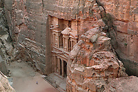 Treasury of the Pharaohs or Khazneh Firaoun, 100 BC - 200 AD, with plaza in front, Petra, Ma'an, Jordan. Originally built as a royal tomb, the treasury is so called after a belief that pirates hid their treasure in an urn held here. Carved into the rock face opposite the end of the Siq, the 40m high treasury has a Hellenistic facade with three bare inner rooms. Petra was the capital and royal city of the Nabateans, Arabic desert nomads. Man walking on plaza shows the scale of the edifice. Picture by Manuel Cohen