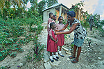 St. Julia Josophot helps her children get ready for school in font of their new home in Lareserve, a village near Jean-Rabel in northwestern Haiti. The family's previous house was destroyed during Hurricane Matthew in 2016, and Church World Service, a member of the ACT Alliance, helped the family build their sturdy new home.