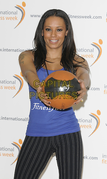 MELANIE BROWN aka MEL B.Launches The International Fitness Week, Fitness First Gym, Tottenham Court Road, London, England, .28th January 2010..photocall half length ball blue black pinstripe striped trousers top tattoo basket holding vest .CAP/CAN.©Can Nguyen/Capital Pictures.