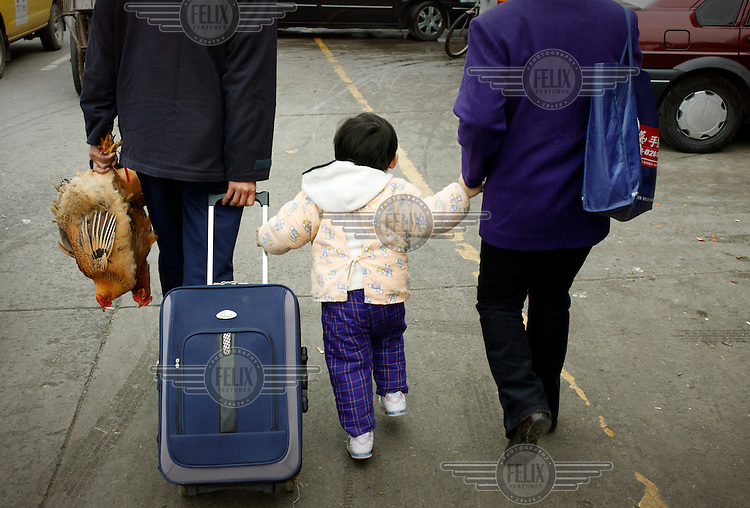 A couple leaving a market with their small child, a suitcase and a pair of live chickens, the latter having been bought to eat for the New Year holiday.