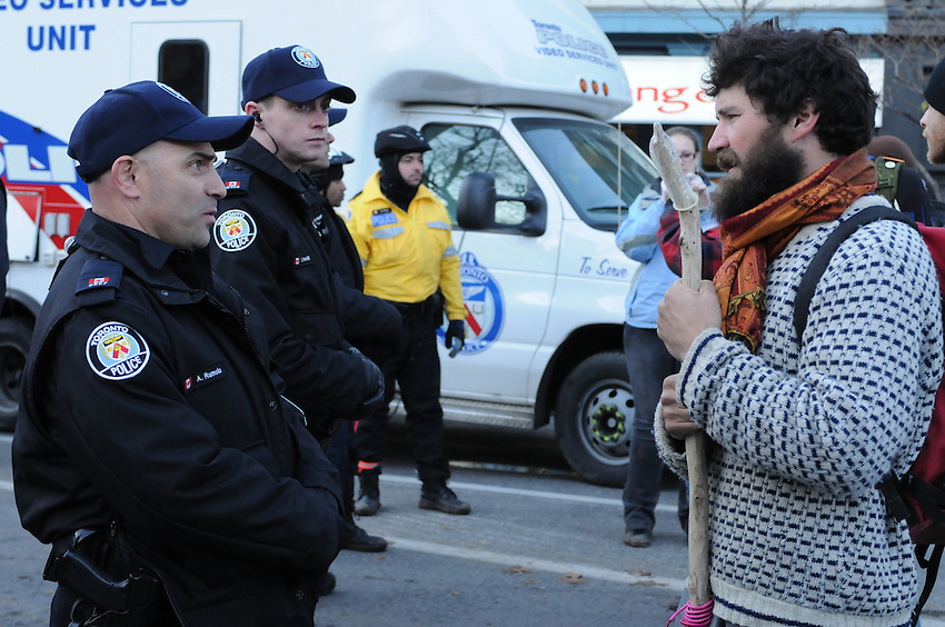 November 23, 2011, wrapping up the eviction, one Toronto Police Service Constable speaks directly with one protester on Adelaide Street, amongst hundreds other Police, protest supporters, City workers and media people at St. James Park.  The Toronto Police Service, municipal works staff and protest coordinators are all winning high praise for the dignified, orderly, respectful and safe transition of the park.