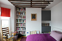 A Victorian home has been given a modernist aesthetic. The master bedroom utilises deep plummy purples and rich oranges and leaving the original roof beams exposed adds a rustic touch.