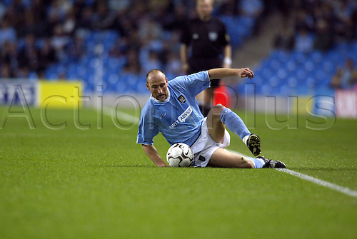 September 24, 2003: City's Australian DANNY TIATTO slides to intercept the ball during the first leg of their First Round UEFA Cup game against Sporting Lokeren played at the City of Manchester Stadium. MANCHESTER CITY 3 v Lokeren 2 Photo: Glyn Kirk/action plus...soccer football 030924 man player