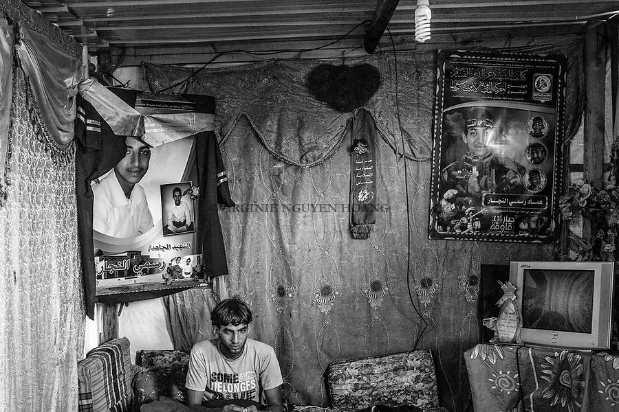 Gaza, Khuzaa: Ahmed Al Najar est assis dans le salon du conteneur o&ugrave; vit sa soeur et sa m&egrave;re. Au-dessus de lui, des photos de son fr&egrave;re tu&eacute; pendant la guerre de 2014. 09/08/15<br /> <br /> Gaza, Khuzaa: Ahmed Al Najar is sitting in the living room of the container where his mother and sister live. Above him, pictures of his brother killed during the 2014 war. 09/08/15