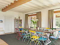 A long, rustic wooden dining table with multicoloured folding chairs in the open plan living/dining area