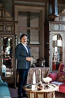 Serdar Gülgün next to an Ottoman-inspired coffee table inlaid with mother of pearl and tortoise shell.