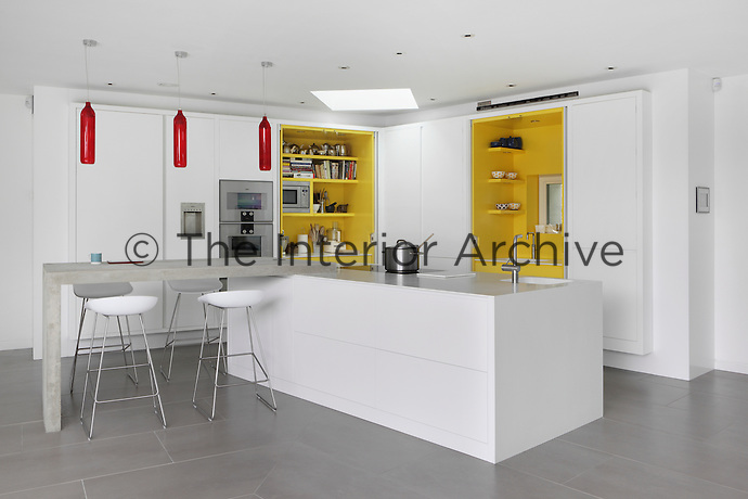 A stylish white kitchen with a central island unit, designed by Chamber Furniture. Three red glass pendant lamps by Tom Kirk hang above the breakfast bar. Concealed behind the white cupboard doors are vibrant yellow recessed units.