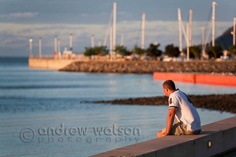 Man looking out from Esplanade at sunset.  Cairns, Queensland, Australia
