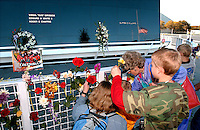 Photo by Rick WIlson--2/1/03--The America Flag is reflected at right as it flies at half-mast as the Balogh (CQ) family of Brooksville, Florida places flowers at the Astronauts Memorial on the grounds of the John F. Kennedy Space center Visitors. They came to the site to pay their respects to the crew of the Space Shuttle Columbia who perished Saturday morning when the craft disintegrated above Texas...