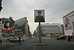 A poster of a Soviet soldiers stares down at passers-by at the site of Checkpoint Charlie. The poster is part of an installation recalling the Soviet and American influence on the formerly-divided city. The Wall was opened 15 years ago on 9th November 1989. ...
