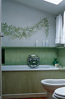 A hand-painted garland adorns one wall of this cool green bathroom