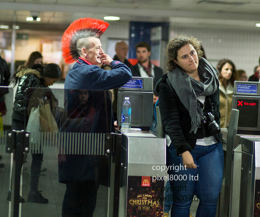 "Pic shows: ""Is this the way to High Barnet?""<br /> <br /> London Underground worker at Oxford Circus with amazing huge mohawk (mohican) hairstyle helps passengers though the ticket barriers at the crowded tube station.<br /> <br /> In 21st century London the dress code is pretty relaxed in most jobs. The colour scheme of his hair did match the red trim of his London Transport uniform.<br /> <br /> This chap, who goes by the name of ""Greg"", gave some xmas cheer to some slightly startled tube passengers.<br /> <br /> One might be forgiven for thinking the station was actually  High Barnet. But this 'punk' certainly made their day.<br /> <br /> <br /> <br /> <br /> picture by Gavin Rodgers/ Pixel8000"