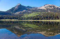 The surrounding forest and mountains are reflected in the still Lost Lake in Colorado