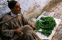 Elderly man selling mint in the street in Fes el Bali, the oldest walled area of Fes, Morocco.