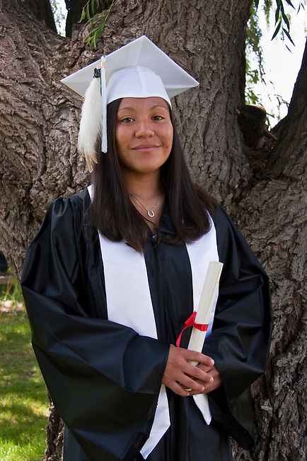 Native American teenage girl dressed in graduation gown and cap holds her highschool graduation diploma