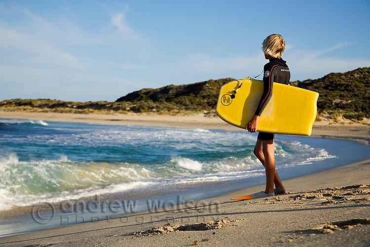 A bodyboarder waits to enter the surf at Margaret River Mouth.   Margaret River, Western Australia, AUSTRALIA.