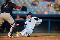 Connecticut Tigers left fielder Daniel Reyes (55) slides home as catcher Alan Marrero (21) waits to receive a throw during a game against the Lowell Spinners on August 26, 2018 at Dodd Stadium in Norwich, Connecticut.  Connecticut defeated Lowell 11-3.  (Mike Janes/Four Seam Images)