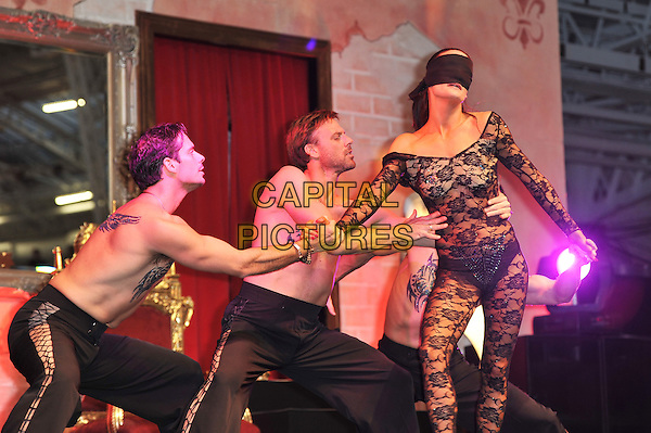 Atmosphere.'Erotica' Exhibition at Olympia Hall, Kensington, London, England, UK, .18th November 2011..half length show dancers dancing on stage blindfold black lace   .CAP/MAR.© Martin Harris/Capital Pictures.