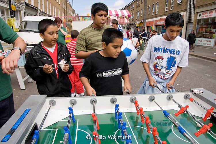 Young boys play table football at Church Street Summer Festival, London.