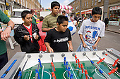Young boys play table football at Church Street Summer Festival, London.