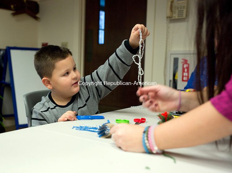 Prospect, CT- 30 November 2015-113015CM02-  Jason Myftari, 5 of Prospect makes a holiday craft with Alessandra Petrine, assistant director at the Prospect library at the library in Prospect on Monday.  The library held the workshop, which focused on making winter hats.  For upcoming events, log onto the web and go to  www.prospectct.com/library.      Christopher Massa Republican-American